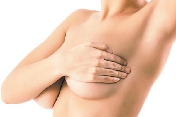 Close up of a mother's midsection after breast lift surgery, her nipples concealed by her hands
