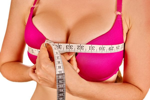 Close up of a woman's large breasts implants covered by a bra and being measured with a measuring tape
